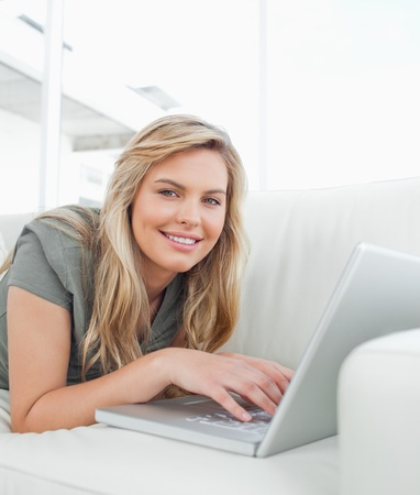 Woman lying on the couch, using her laptop as she smiles and looks forward. photo