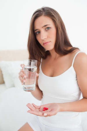 A woman is looking worried as she is deciding about taking the pills with a glass of water in her other hand. photo