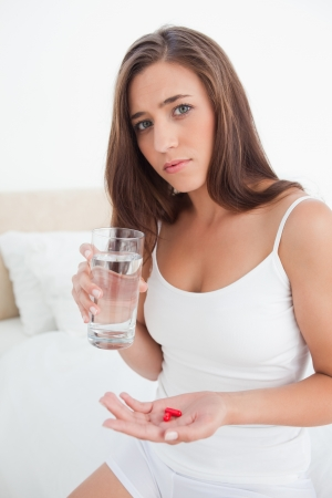 A woman looking forward about to take two red pills with a glass of water. photo