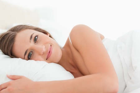 A woman with eyes open and smiling, lying in bed. photo