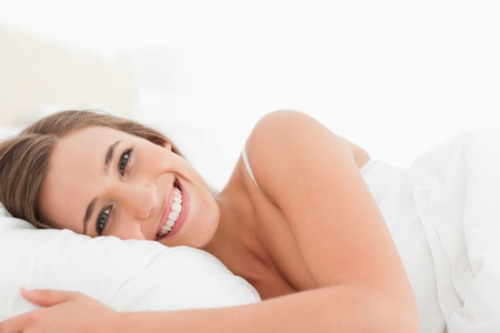 A woman smiling brightly as she lies awake in bed. photo