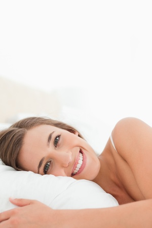 A close up shot of a woman smiling brightly in bed. photo