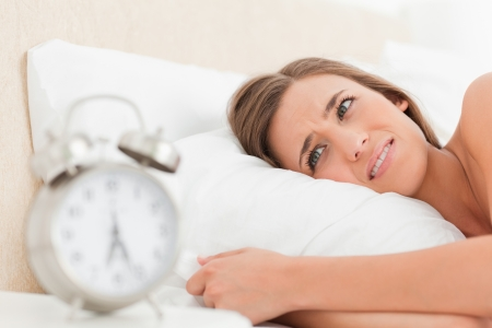 A woman in bed awake and slightly annoyed by her alarm clock. photo
