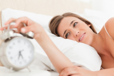 A woman using her hand to reach and turn off her alarm clock. Stock Photo - 13650849