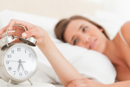 Focus on the alarm clock as woman reaches over to silence its alarm. photo