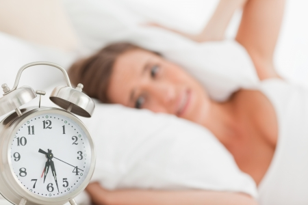 A woman blocks her ears with a pillow as her alarm clock goes off. Stock Photo - 13650695