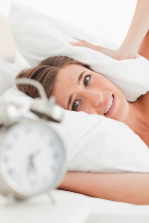 A close up shot of the woman with a pillow over her ears to drown out the alarm. Stock Photo - 13650778