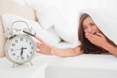 A woman is reaching out to silence her alarm clock while underneath her blanket in bed. Stock Photo - 13650193