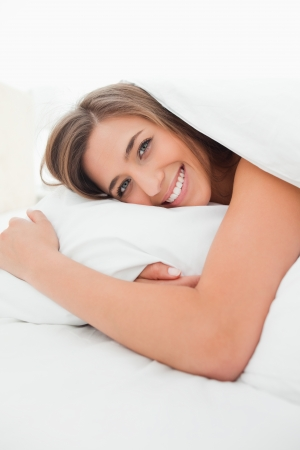 A smiling woman awake in bed looking forward with her head on the pillow. photo