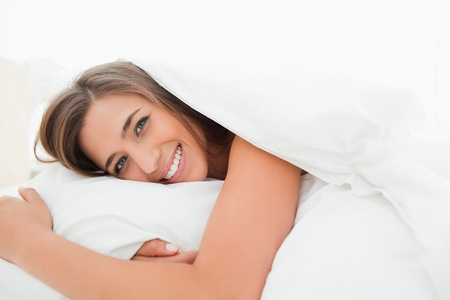 A woman smiling as she lies on bed with her head on the pillow. photo