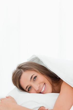 A vertical shot of a woman in bed, smiling as she rests her head on the pillow. photo