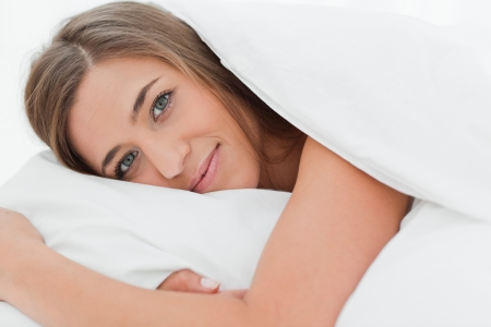 A close up shot of a woman lying in bed with her head on the pillow as she looks forward. photo