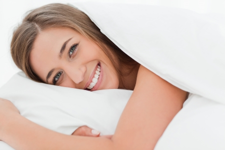 A close up shot of a woman in bed smiling as she has her head on the pillow. photo