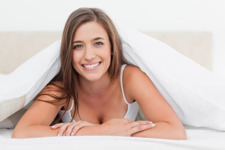 A smiling woman looking straight ahead as she lies at the end of the bed. photo
