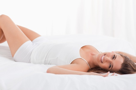 A woman lying on her back while looking forward and smiling, lying on the bed. photo