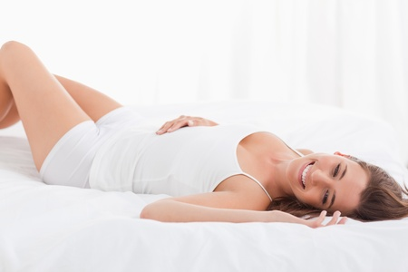 A smiling woman is lying on her back while on the bed. photo