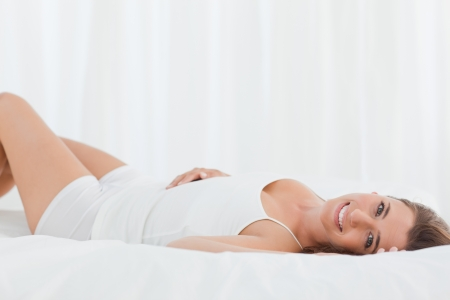 A woman looking forward smiling while lying on the bed on her back. photo