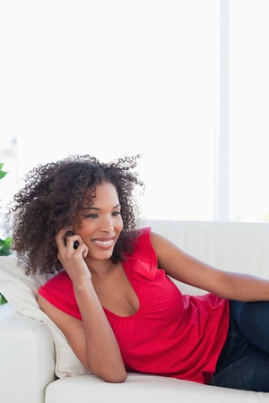 A woman lying on the couch making a phone call and smiling. photo