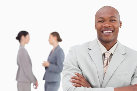 Smiling businessman with folded arms and co-workers behind him against a white background