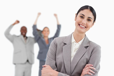 Smiling saleswoman with cheering co-workers behind her against a white background photo