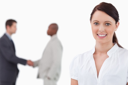 Smiling saleswoman with hand shaking colleagues behind her against a white background photo