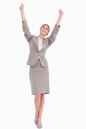 Young businesswoman with arms raised against a white background photo