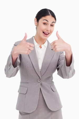 Cheering businesswoman giving thumbs up against a white background Stock Photo - 13675282