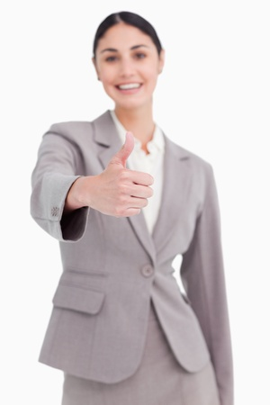 Thumb up given by smiling businesswoman against a white background photo