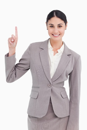 Smiling young businesswoman pointing up against a white background photo