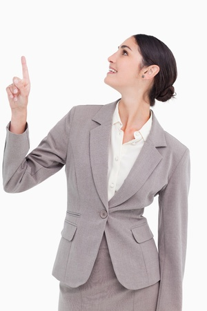 Smiling businesswoman looking and pointing up against a white background photo