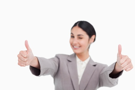Thumbs up given by smiling young businesswoman against a white background photo