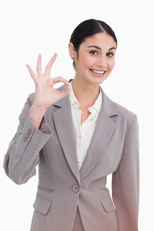 Young businesswoman giving approval against a white background photo
