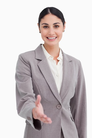 Smiling businesswoman offering her hand against a white background photo