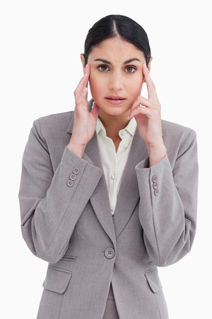Young saleswoman with headache against a white background photo
