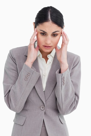 Young saleswoman experiencing a headache against a white background photo