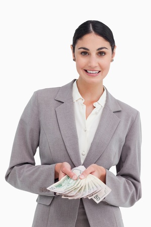 Smiling businesswoman showing her money against a white background photo