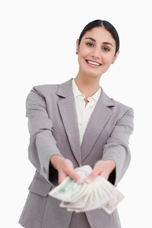 Smiling businesswoman handing over money against a white background photo