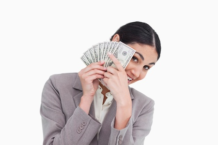 Young saleswoman covering her face with bank notes against a white background photo