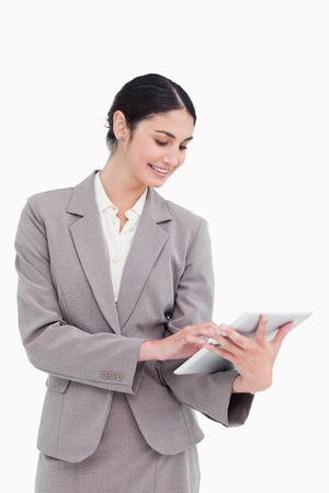 Smiling saleswoman using her tablet computer against a white background photo