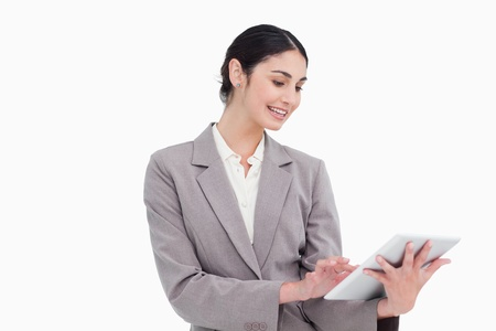 Smiling young businesswoman using tablet computer against a white background photo