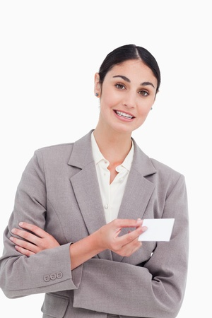 Saleswoman with arms folded and business card against a white background photo