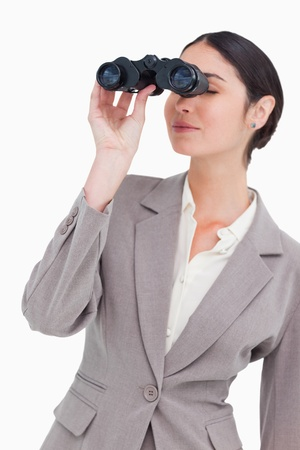 Businesswoman looking through spy glasses against a white background photo