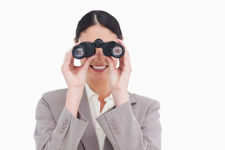 Smiling businesswoman looking through spy glasses against a white background photo