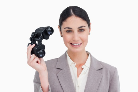 Businesswoman with spy glasses against a white background photo