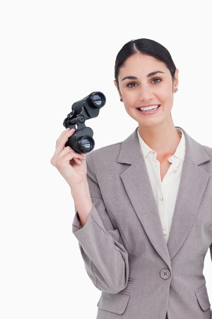 Smiling businesswoman with spy glasses against a white background Stock Photo - 13673830