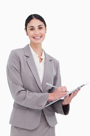 Smiling businesswoman ready to take notes against a white background photo
