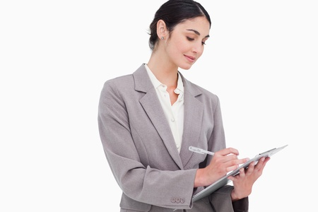 Businesswoman taking notes against a white background Stock Photo - 13650581
