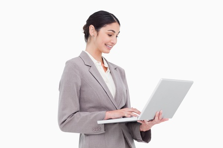 Side view of businesswoman using laptop against a white background photo