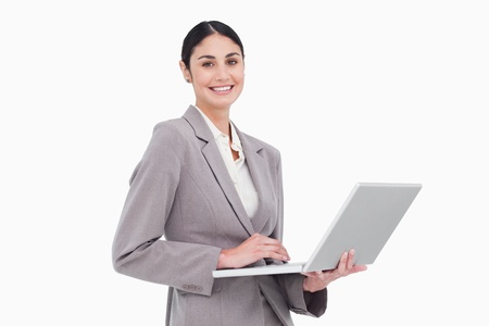 Smiling businesswoman with her laptop against a white background photo