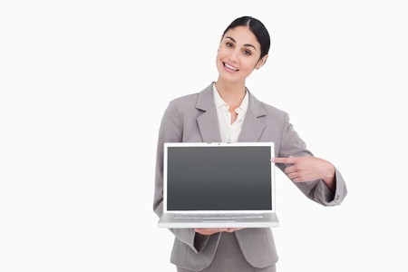 Businesswoman pointing at screen of her laptop against a white background photo